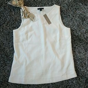 Sleeveless cream-colored blouse with sequin bow.